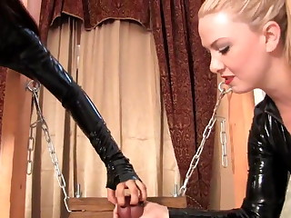 THESE TWO MISTRESSES CLAN IN LATEX CATSUITS AND CORSETS CBT THE HAPLESS MALE SLAVE